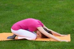 Bella donna dai capelli marrone con gli occhi chiusi che fanno allungamento della parte posteriore durante gli esercizi nella pos Immagine Stock Libera da Diritti
