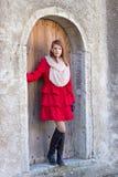 Bella donna dai capelli rossi che posa davanti alla vecchia porta Immagine Stock