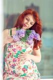 Bella donna dai capelli rossi incinta che si siede su un davanzale della finestra alla finestra immagine stock