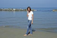 Bella donna dalla spiaggia con un cellulare Fotografia Stock