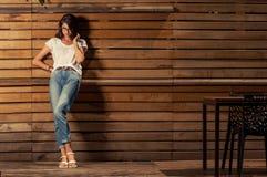 Bella donna dei pantaloni a vita bassa che si appoggia recinto di legno fotografie stock libere da diritti