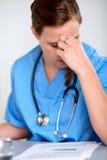 Bella donna del medico di affaticamento con uno stetoscopio Immagine Stock