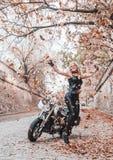 Bella donna del motociclista che posa con il motociclo all'aperto fotografia stock libera da diritti