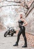 Bella donna del motociclista che posa con il motociclo all'aperto immagine stock
