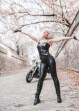 Bella donna del motociclista che posa con il motociclo all'aperto immagini stock