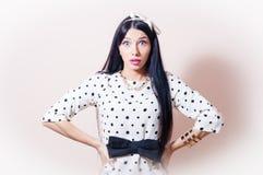 Bella donna del pinup di fascino castana in vestito bianco con il pois, capelli lunghi che sembrano sorpresi su fondo bianco Fotografia Stock Libera da Diritti