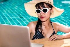 Bella donna del ritratto che utilizza computer portatile dalla piscina nel hote Fotografie Stock Libere da Diritti