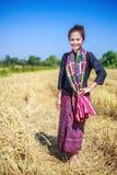 Bella donna dell'agricoltore con la paglia nel campo Immagine Stock