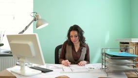 Bella donna dell'architetto che lavora ad un nuovo progetto al suo scrittorio stock footage