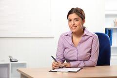 Bella donna dell'ufficio che si siede alla scrittura dello scrittorio Immagini Stock