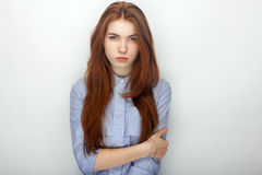 Bella donna della giovane testarossa arrabbiata seria in ritratto della camicia su un fondo bianco che si abbraccia immagine stock