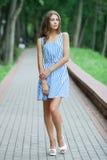 Bella donna della primavera in vestito da estate che posa nel parco verde che gode del fine settimana Ragazza caucasica allegra e Fotografie Stock