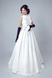 Bella donna della sposa che posa in vestito da sposa isolato sulla b grigia fotografie stock