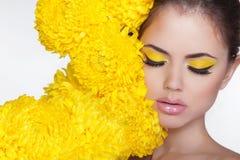 Bella donna della stazione termale sopra i fiori del crisantemo. Osserva il trucco. Bea Fotografie Stock Libere da Diritti