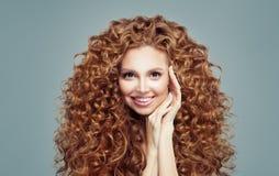 Bella donna della testarossa con capelli ricci lunghi isolati su bianco Concetto di Haircare immagini stock
