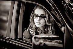 Bella donna della testarossa nell'automobile fotografie stock libere da diritti