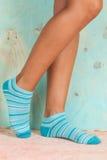 Bella donna delle gambe con i calzini che stanno sulla punta dei piedi sul pavimento di legno immagine stock