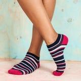 Bella donna delle gambe con i calzini che stanno sulla punta dei piedi sul pavimento di legno fotografia stock libera da diritti