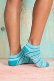 Bella donna delle gambe con i calzini che stanno sulla punta dei piedi sul pavimento di legno immagini stock libere da diritti