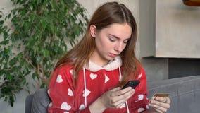 Bella donna dello zenzero che paga l'acquisto di Internet con la carta di credito sul sulla suoi telefono, smartphone della tenut video d archivio
