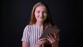 Bella donna dello zenzero che sorride e che tiene compressa con il chromakey, stante isolato sul fondo nero dello studio video d archivio