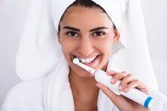 Bella donna in denti di spazzolatura dell'accappatoio immagine stock libera da diritti