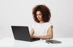 Bella donna di affari africana che esamina computer portatile sopra fondo bianco Immagini Stock Libere da Diritti