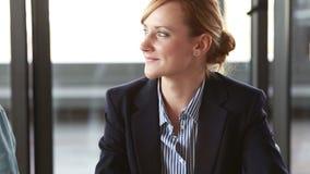 Bella donna di affari che annuisce col capo e che sorride nel corso della riunione nell'auditorium video d archivio