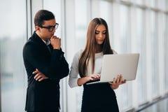 Bella donna di affari che ascolta il suo collega alla riunione circa l'ufficio panoramico dei cambiamenti Uomo di affari indicato Fotografie Stock