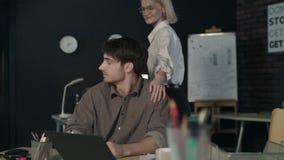 Bella donna di affari che bisbiglia al giovane collega dell'orecchio nel luogo di lavoro archivi video