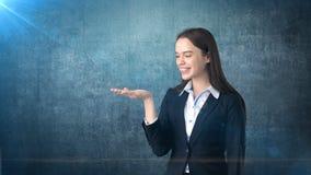 Bella donna di affari che esamina la sua mano e che sorride, fondo blu scuro Fotografie Stock Libere da Diritti