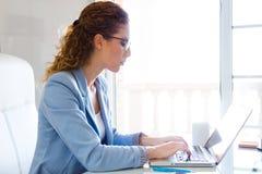 Bella donna di affari che lavora con il suo computer portatile nell'ufficio Fotografie Stock