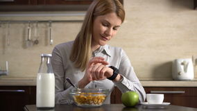 Bella donna di affari che mangia prima colazione e che per mezzo del suo orologio astuto Internet di lettura rapida Notizie della archivi video