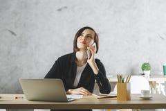 Bella donna di affari che per mezzo dello smartphone nel luogo di lavoro Fotografie Stock Libere da Diritti
