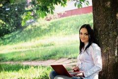 Bella donna di affari che si siede con il computer portatile sotto un albero Immagini Stock
