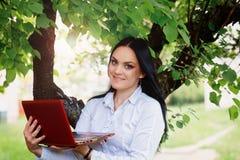Bella donna di affari che si siede con il computer portatile sotto un albero Fotografie Stock