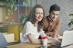 Bella donna di affari con capelli ricci che sorride, riunita insieme al partner, discutente idea creativa nell'ufficio Fotografia Stock