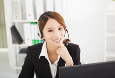 Bella donna di affari con la cuffia avricolare in ufficio Fotografia Stock
