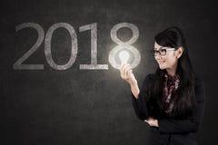 Bella donna di affari con la lampadina ed i numeri 2018 Fotografia Stock