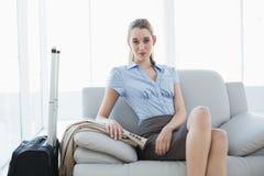 Bella donna di affari elegante che posa seduta sullo strato accanto alla sua valigia Immagine Stock