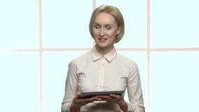 Bella donna di affari facendo uso del dispositivo della compressa video d archivio