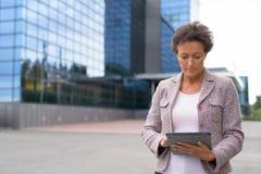 Bella donna di affari matura Using Digital Tablet all'aperto immagini stock libere da diritti