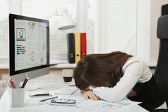 Bella donna di affari nel funzionamento di vetro e del vestito al computer con i documenti in ufficio leggero immagini stock libere da diritti