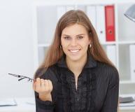 Bella donna di affari sorridente che giudica i vetri disponibili Immagini Stock