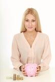 Bella donna di affari sorridente che scuote porcellino salvadanaio Fotografia Stock Libera da Diritti