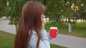 Bella donna di affari in vetri che parla sullo smartphone e sul caffè bevente mentre camminando nel parco in autunno stock footage