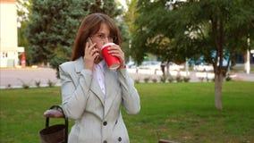 Bella donna di affari in vetri che parla sullo smartphone e sul caffè bevente mentre camminando nel parco in autunno fine archivi video