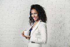 Bella donna di colore con la tazza in mani sul fondo della parete di mattoni Immagini Stock