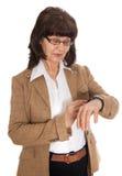 Bella donna di età matura che esamina orologio Fotografie Stock Libere da Diritti