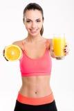 Bella donna di forma fisica che dà un succo e una metà dell'arancia Fotografia Stock